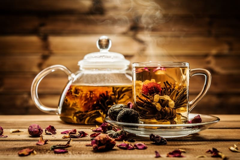 Teapot and glass cup with blooming tea flower