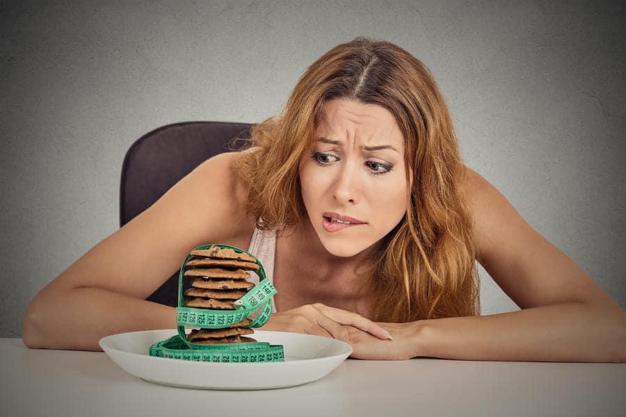 Жена, която гледа сладки бисквитки и й се иска да ги изяде
