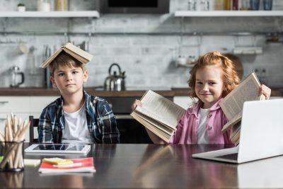 Деца, с книги на главата, намиращи се в кухнята и видимо забавляващи се.