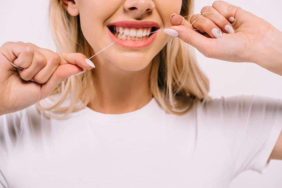 Млада дама, която чисти зъбите си с конец, облечена в бяла тениска. Поддържане на оралната хигиена.