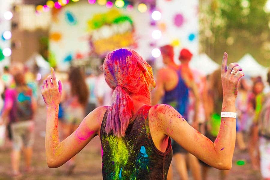 Момиче, обърнато с гръб, цялото в различни цветове, по време на празника на цветовете Холи.