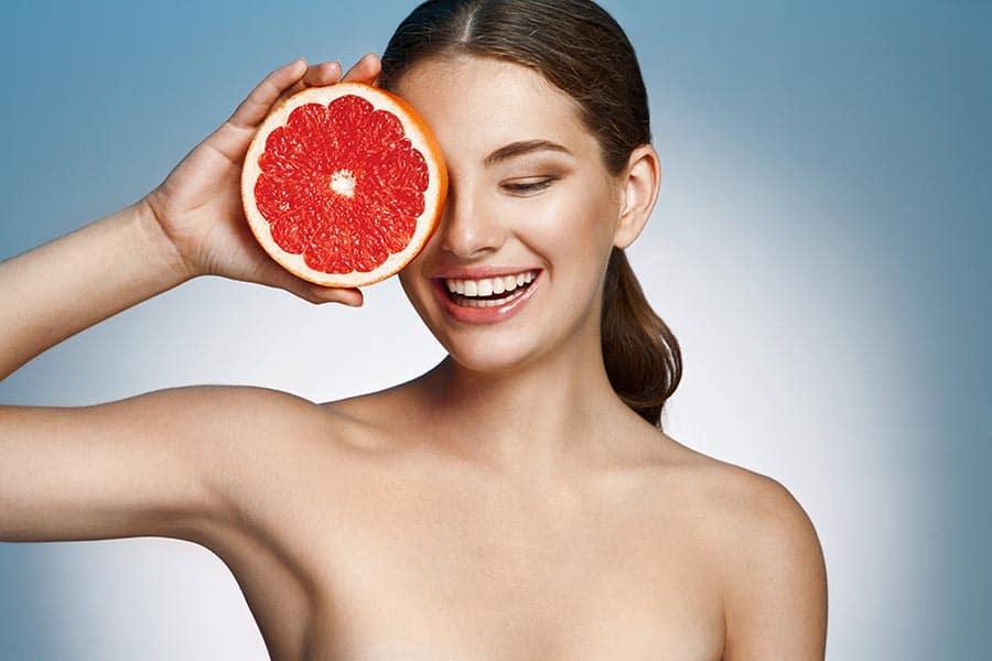 Млада дама с красива кожа, държата грейпфрут