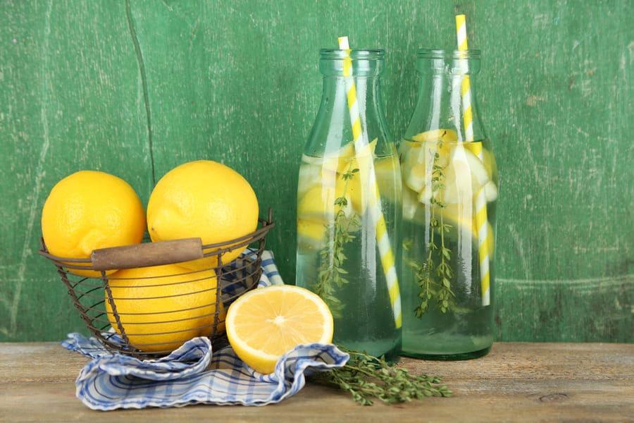 Две бутилки с вода и резани лимон, гарнирани с лимони в кошница.