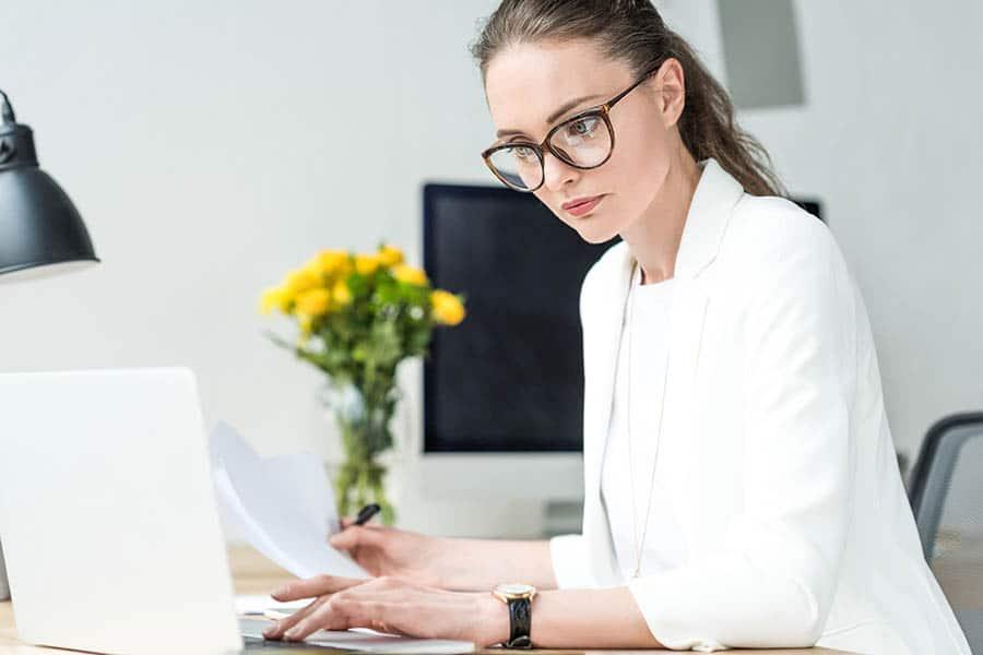 Млада дама, съсредоточена в работата си на компютъра. Работи заседнало, в офис.
