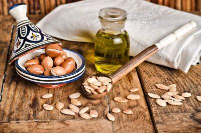 Арганови семена, от които е приготвено араганово масло. То е показано на заден фон.