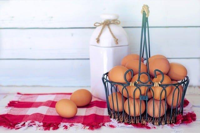 Кошница с яйца и кутия прясно мляко върху червена покривка.