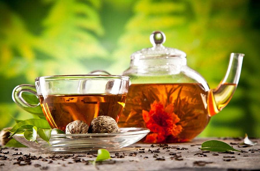 Чаша чай с чайник и поставени орехи в чинийка.