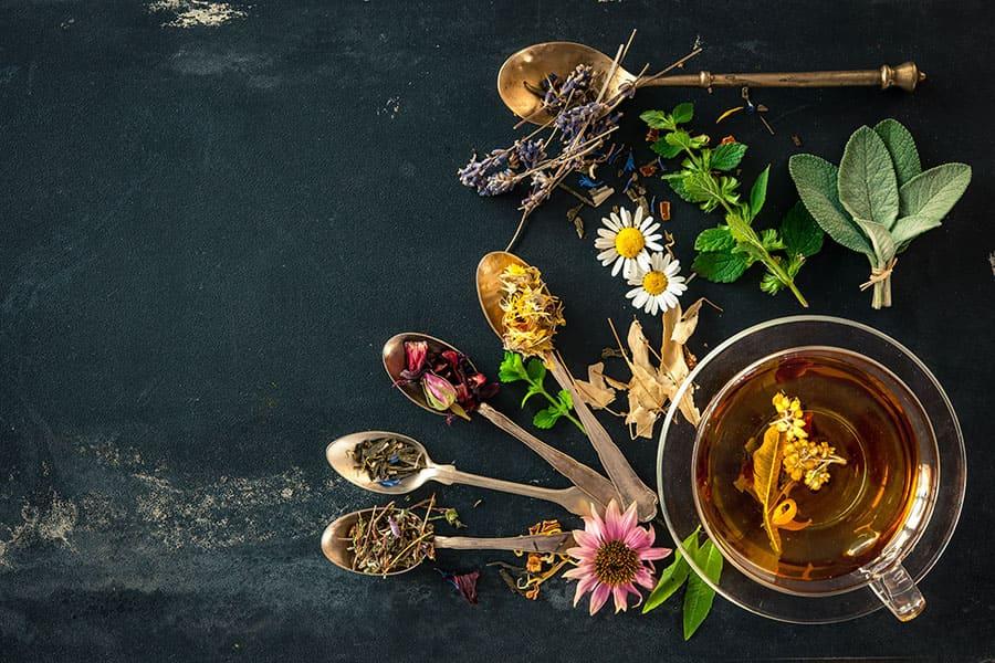 Видове чай, разположени в насипен вид в малки лъчижки, около чаша горещ чай. Билки за отслабване.