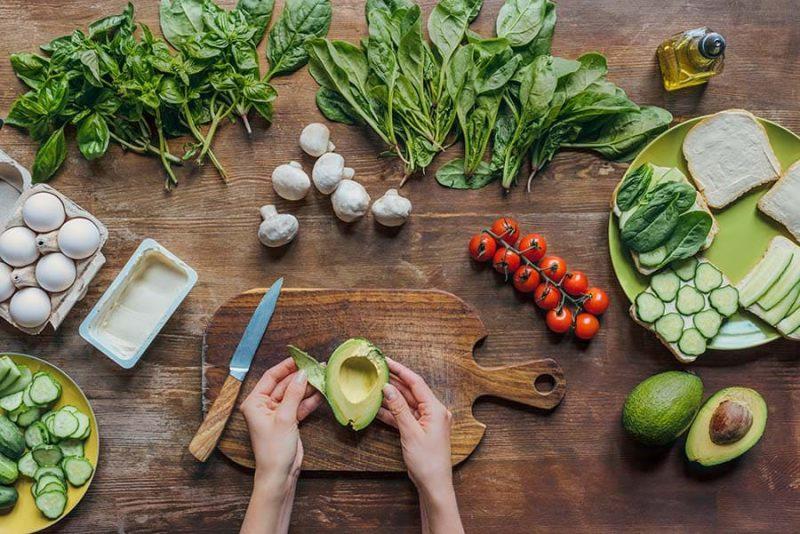 Зеленчуци, повечето от които богати на мазнини. Две ръце, които режат авокадо.