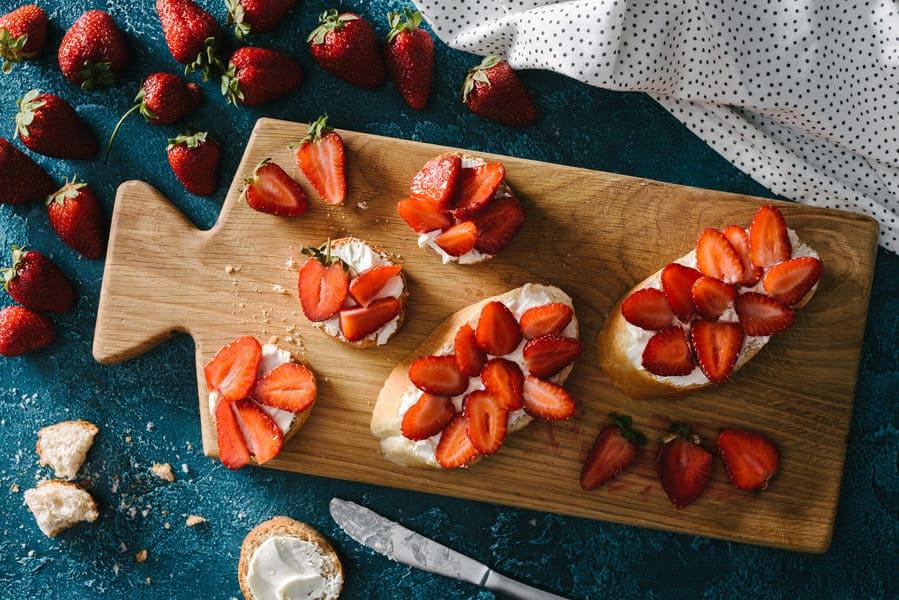 брускети с маскарпоне ягоди. Разположени върху дъска и готови за сервиране.