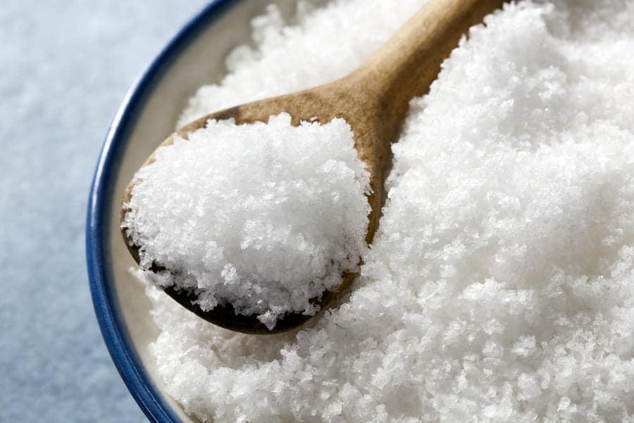 Лъжица с морска сол, над купа пълна с морска сол.