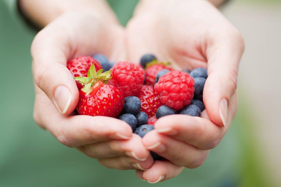 Бери плодове в шепа ръка, на фона на зелена растителност.