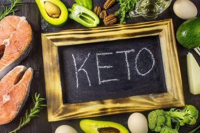 Авокадо, ядки, сьомга, яйца и зеленчуци, отрупани на маса. Кетоза.