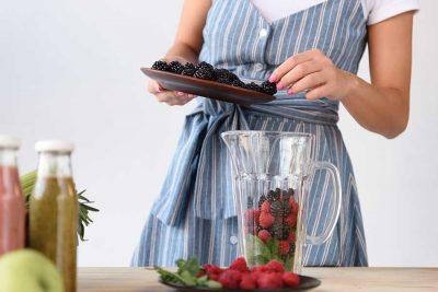 Млада жена, която прави смути от бери плодове. Детокс за лятото с плодове.