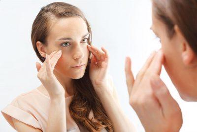 Млада жена, която гледа своите бръчки. Проверява зрението си и нивото на хиалуронова киселина в тялото.