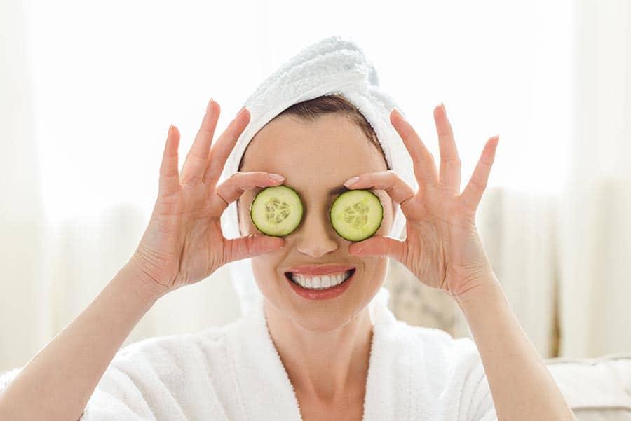 Красива дама, сложила две резенчета краставица на учите си. С хавлия на косата, готова за релаксиращи процедури. Подпомагане за добро зрение.