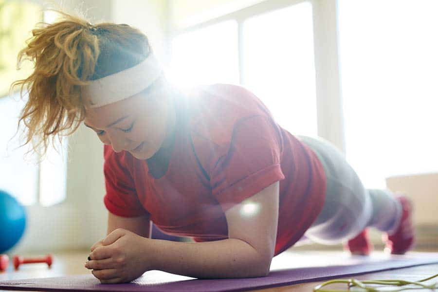Portrait of young obese woman working out on yoga mat in fitness studio: holding plank exercise with effort to lose weight