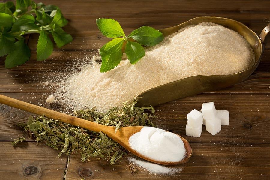 Естествения подсладител стевия срещу вреднта бяла захар. Листенца от стевия, стевия на кристали и бяла захар.