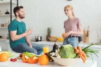 Млада двойка, хапваща плодове и зеленчуци в кухнята. На преден план са всички свежи зеленчуци.