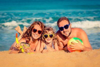 Семейство млади хора, щастливи на плажа по време на лятната им почивка.