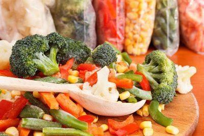 Микс от замразени зеленчуци, поставени на дървена дъска и лъжица.