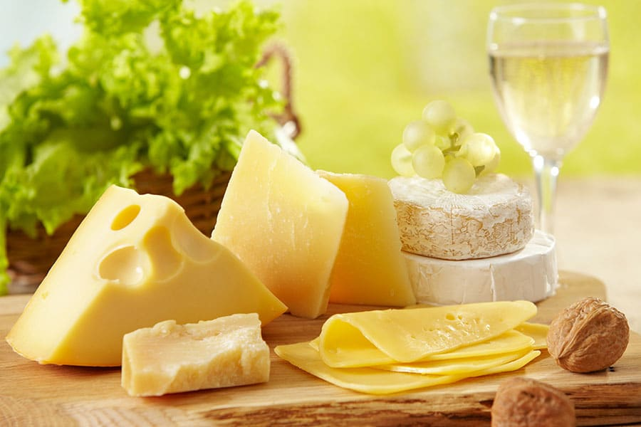 Различни видове сирена, подредени на дървена дъска за рязане. Сирената са изключително полезни източници на пробиотик.