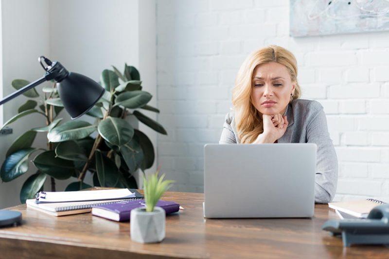 Млада дама, в офиса, отекчена от задължения. Стрес след отпуска в офиса. Липса на работно настроение.