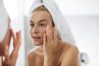 Beautiful Caucasian woman in towels looking her face in mirror and putting creme on.