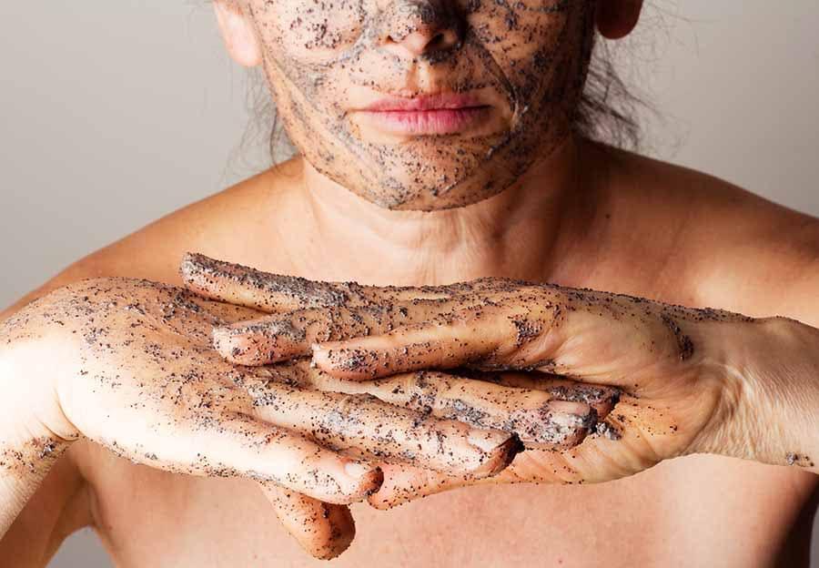 Млада жена с нанесен ексфолиант по ръцете и лицето. Домшано ексфолиране на кожата на тялото.