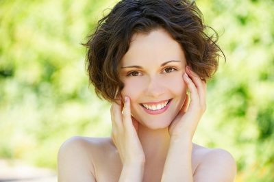 Outside close-up portrait of beautiful young happy woman with fresh and clean skin