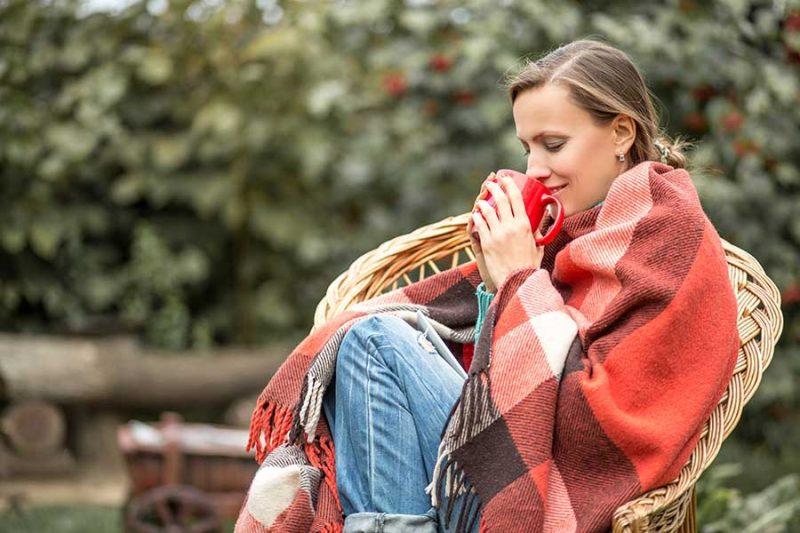 Жена през есента, завита с одеало и пиеща чай. Подсилване на имунитета през есента.