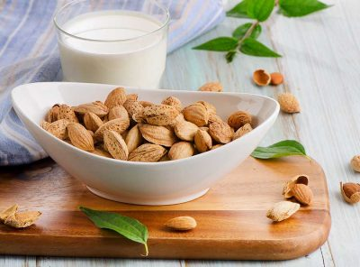Almond milk in glass with almonds. Selective focus
