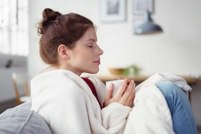 woman holding a cup of warm tea while relaxing on the sofa with eyes shut