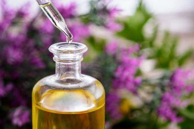 Конопено масло със стъклена пипетка, на лилав фон на цветя.