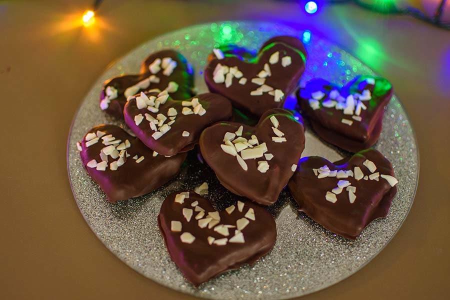 Коледни шоколадови сладки под формата на сърчица, украсени с коледни светлини.