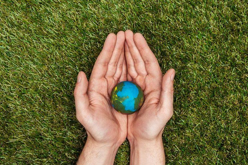 Две ръце, които държат омалена версия на земята в дланите си. Поставени са на зелена трева.