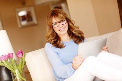 Portrait of attractive businesswoman working at home. Mature professional woman sitting at home at sofa and holding hands digital tablet while holding online.