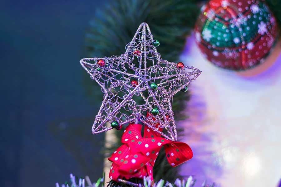 Коледната украса - коледна звездичка на върха на елха, осветена от коледни лампички.