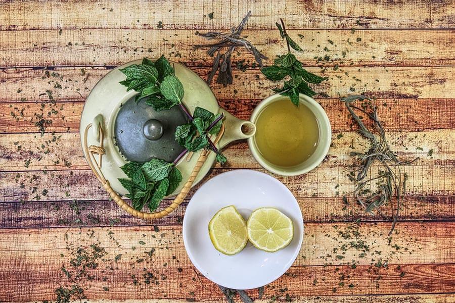 Чайник с черен чай за отслабване и резени лимон, направен от билки за силен имунитет.
